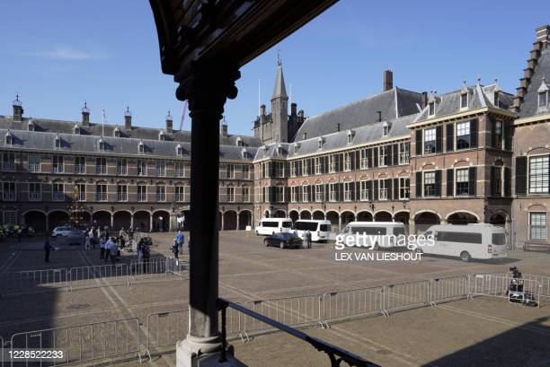 Buses are parked outside the Binnenhof to bring Members of Parliament to the Grote Kerk on Prinsjesdag in The Hague on September 15, 2020. /...