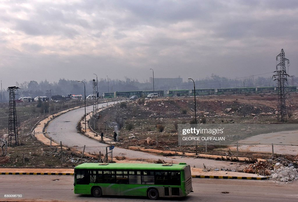 TOPSHOT - Buses are seen during an evacuation operation of Syrian rebel fighters and civilians from a opposition-held area of Aleppo towards rebel-held territory in the west of Aleppo's province on December 16, 2016. Russia announced it was negotiating with the Syrian opposition and seeking a nationwide ceasefire, as the evacuation of civilians and fighters from the last rebel-held parts of Aleppo entered a second day. The Syrian Observatory for Human Rights, a Britain-based monitor of the war, estimated some 8,500 people had left so far, including around 3,000 rebel fighters. Syrian state media reported a figure of around 8,000. / AFP / George OURFALIAN