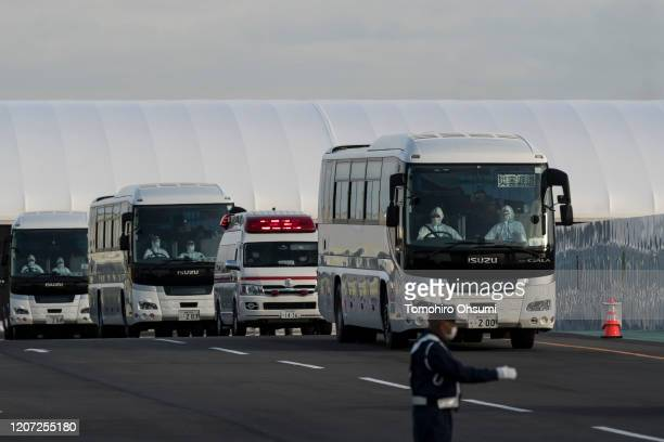 Buses carrying passengers who disembarked the quarantined Diamond Princess cruise ship and emergency vehicle drive at the Daikoku Pier on February 19...