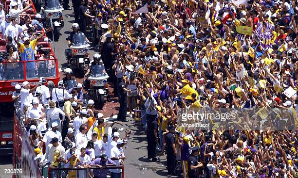 Buses carrying team members including Kobe Bryant stroll down Figueroa Street during the victory parade for the Los Angeles Lakers on June 14 2002 in...