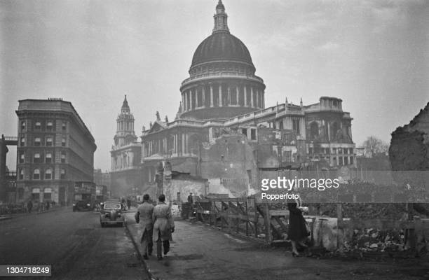 Buses, cars and pedestrians drive and walk along St Paul's Churchyard and Cannon Street beside Blitz damaged bomb sites in front of St Paul's...