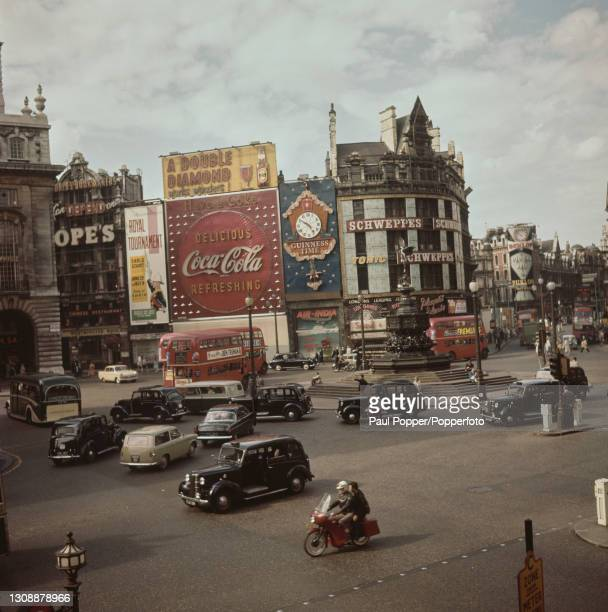 Buses, cars, taxis and motorcycles pass through Piccadilly Circus and up Shaftesbury Avenue in London circa 1960. Neon advertising signs, including...