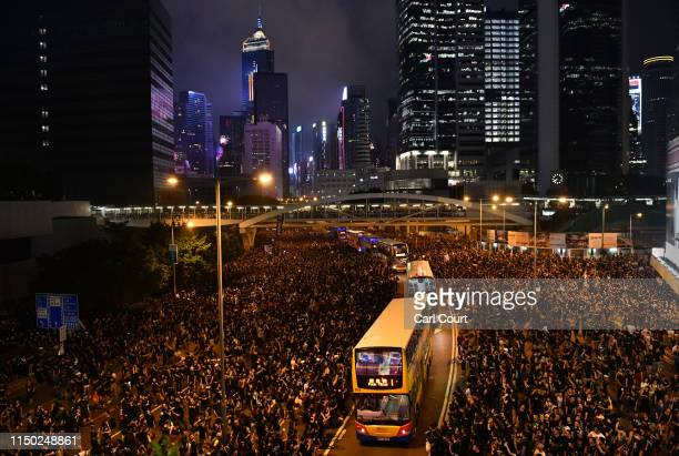 Buses drive through crowds of protesters outside the Legislative Council building as they demonstrate against the nowsuspended extradition bill on...