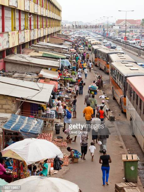 Buses lined up alongside stalls and traders at the congested Kaneshie Market. A busy street scene. Accra, Ghana