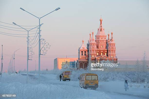 Buses pass a pedestrian on a frozen road near the orthodox Church of Saint Seraphim of Sarov in Udachny Sakha Republic Russia on Thursday Dec 12 2013...
