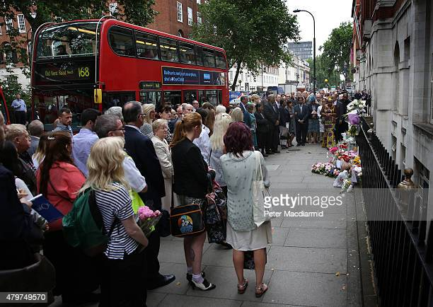 Buses pass by as family members attend a remembrance ceremony at the spot where 13 people were killed in the London bombings on July 7 2015 in London...