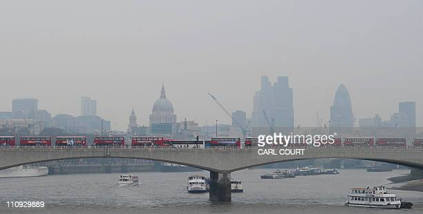 Buses queue along Waterloo Bridge as protesters march along the Embankment in central London on March 26 in a mass demonstration against government...