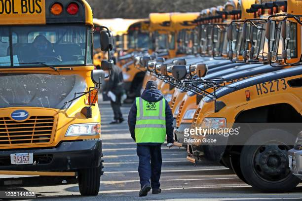 Buses return to the school bus lot on Freeport Street after the morning run to Boston schools on March 9, 2021.