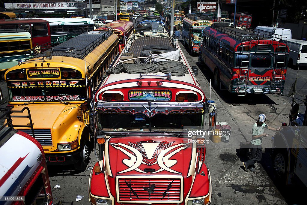 Buses wait for passengers at the Terminal Market in Guatemala City, Guatemala, on Wednesday, Nov. 23, 2011. Foreign direct investment in Guatemala will stagnate this year at about $668 million, after rising 22 percent in 2010, according to the International Monetary Fund (IMF). Photographer: Victor J. Blue/Bloomberg via Getty Images