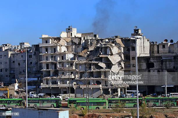 Buses which will be used to evacuate rebel fighters and their families from rebelheld areas of Aleppo are seen waiting on December 15 2016 Russia...