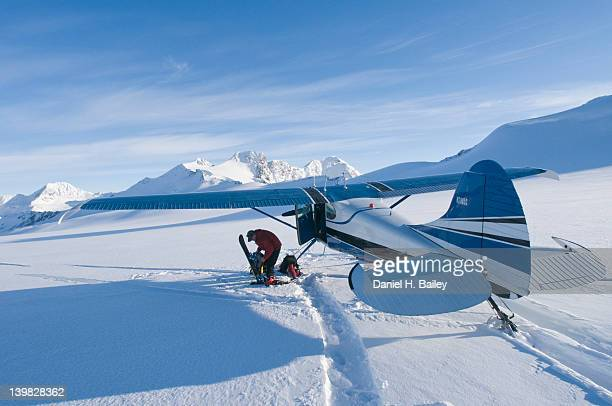 bush pilot with a snowboard next to his cessna 170, on skis on the eagle glacier, chugach mountains, alaska - chugach mountains stock pictures, royalty-free photos & images