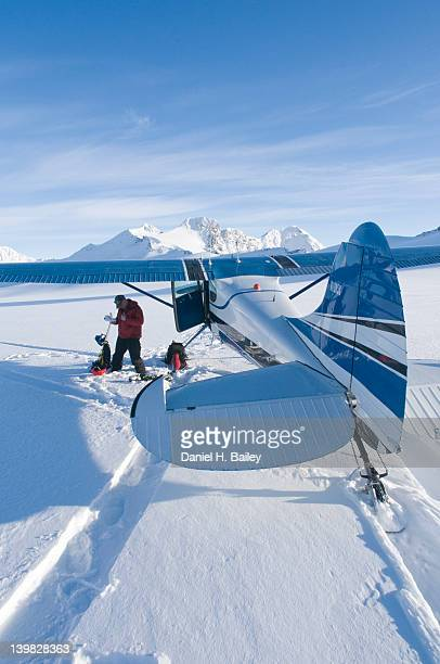 bush pilot with his cessna 170, on skis on the eagle glacier, chugach mountains, alaska - chugach mountains stock pictures, royalty-free photos & images