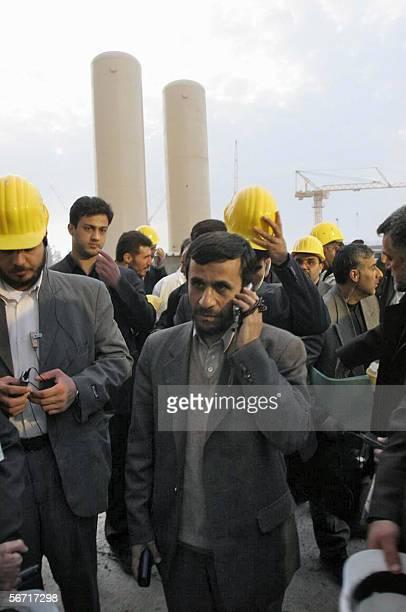 Iranian President Mahmoud Ahmadinejad talks on his mobile phone during a tour of the Bushehr nuclear power plant 01 February 2006 Iran's hardline...
