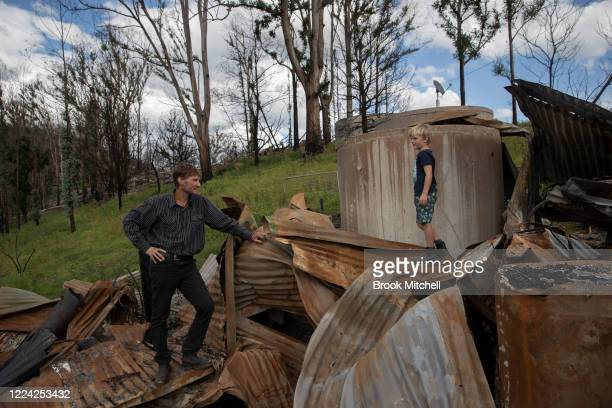 Bushfire survivor Ian Livingston and his son Sydney are pictured amongst the ruins of their family home lost to the New Year's Day bushfires on May...