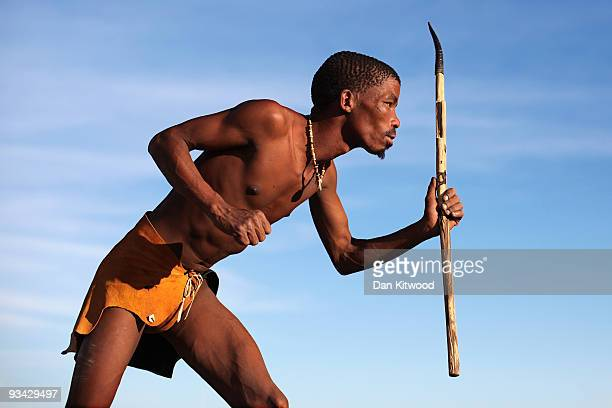 A bushman from the Khomani San community strikes a traditional pose in the Southern Kalahari desert on October 16 2009 in the Kalahari South Africa...