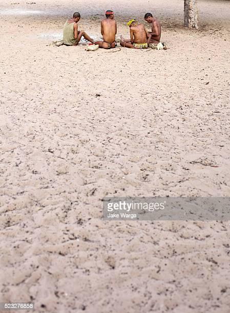 bushman hunters sitting in village, nhoma camp, bushman/ju'hoansi people, namibia - jake warga stock photos and pictures