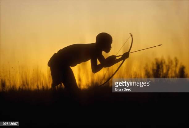 Bushman or San against setting sun hunting Wildebeeste with bow and arrow Etosha Pan Namibia