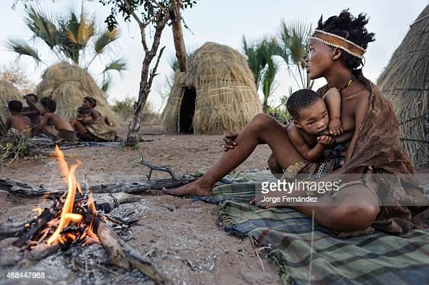 Bushmen baby nursing her mother's breast milk Kalahari desert