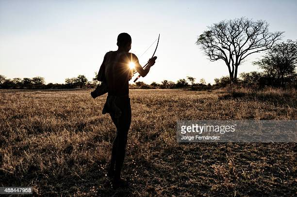 Bushmen getting ready to shoot with his bow against the sunset in the Kalahari desert Namibia Africa