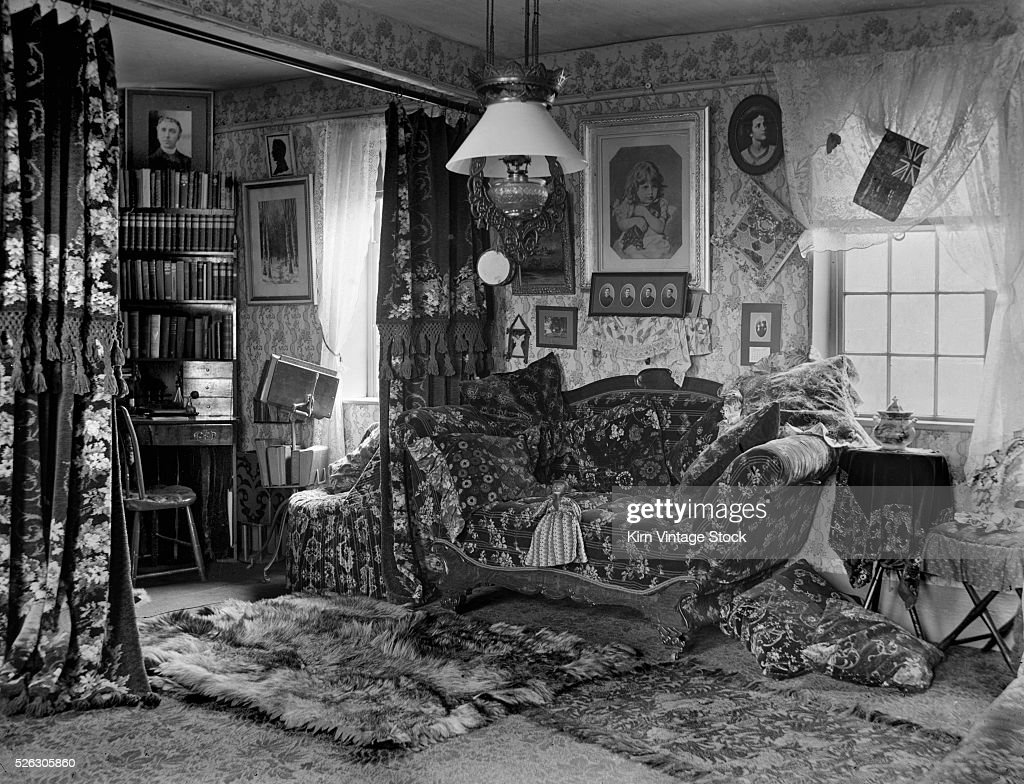 Busily Decorated Living Room In Turn Of The Century American.