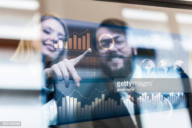 busines couple discussing business profit on a modern interface - touch sensitive stock pictures, royalty-free photos & images