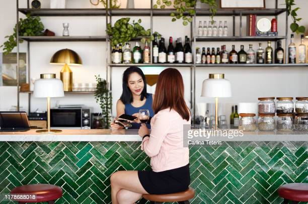 Busineses woman making contactless payment in a modern bar