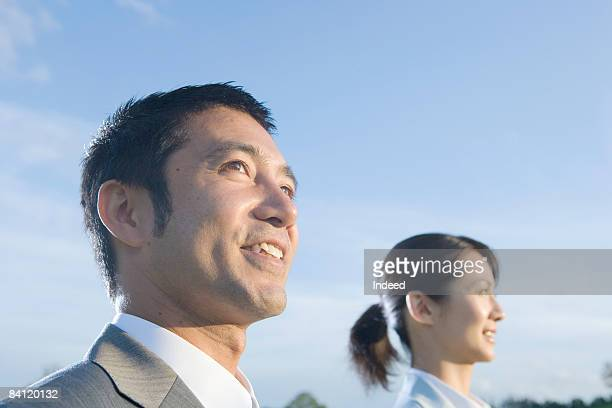 businesman and woman smiling and looking away - ローアングル ストックフォトと画像