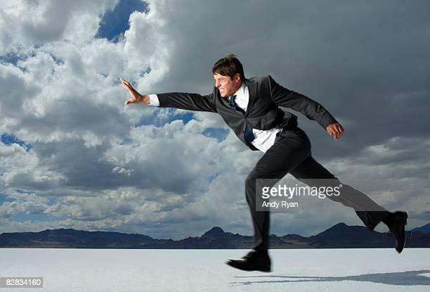 Businesman lunging in desert