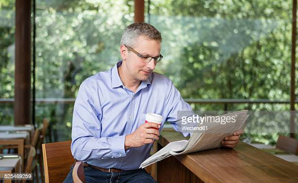 Businesman reading newspaper in cafe