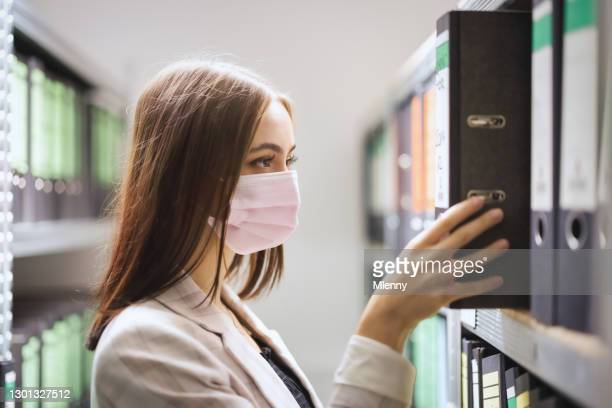 business accountant looking for files in financial archive wearing covid-19 face mask - mlenny stock pictures, royalty-free photos & images