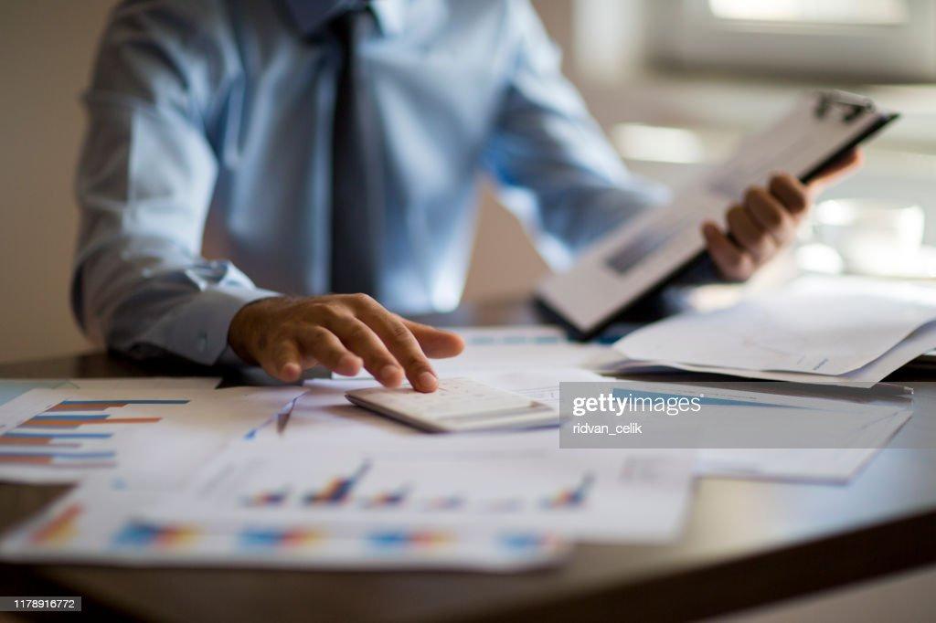 Business Accounting Konzept, Geschäftsmann mit Taschenrechner mit Computer-Laptop, Budget und Leihpapier im Büro. : Stock-Foto