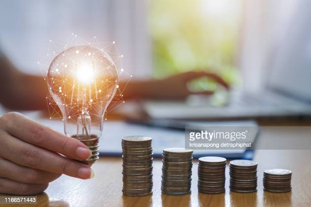 business accounting with saving money with hand holding lightbulb concept financial background - ersparnisse stock-fotos und bilder