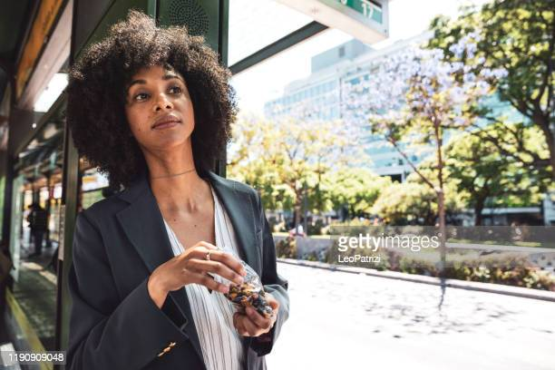 business afro american woman at bus stop in downtown - snack stock pictures, royalty-free photos & images