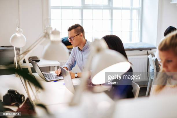 business and coworking with multi-ethnic professionals in developed countries - hot desking stock pictures, royalty-free photos & images