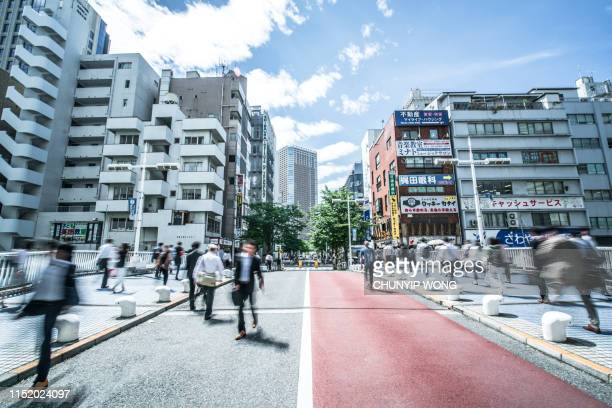 business and office workers going to work in a fast blur during morning rush hour in tokyo, japan - busy sidewalk stock pictures, royalty-free photos & images