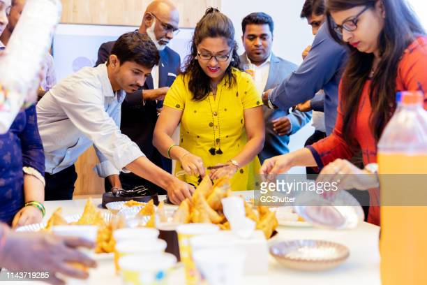 business anniversary celebration at the office - samosa stock photos and pictures