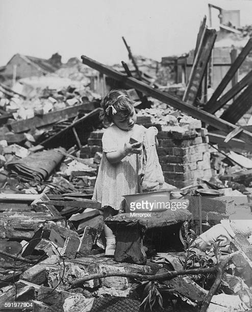 Business as usual for this little girl as she changes her toy doll's clothes surrounded by wreckage and devastation of bombed buildings during the...
