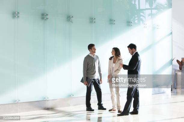business associates chatting in office corridor - drei personen stock-fotos und bilder