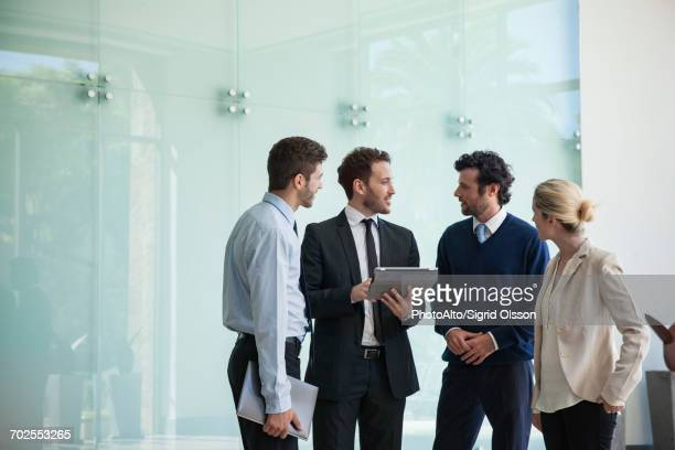 business associates collaborating using digital tablet - full suit stock pictures, royalty-free photos & images