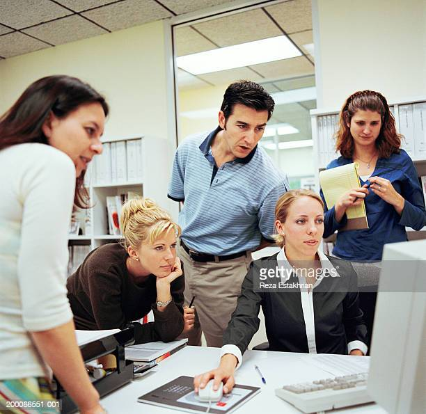 Business associates in office, looking at computer screen, front view