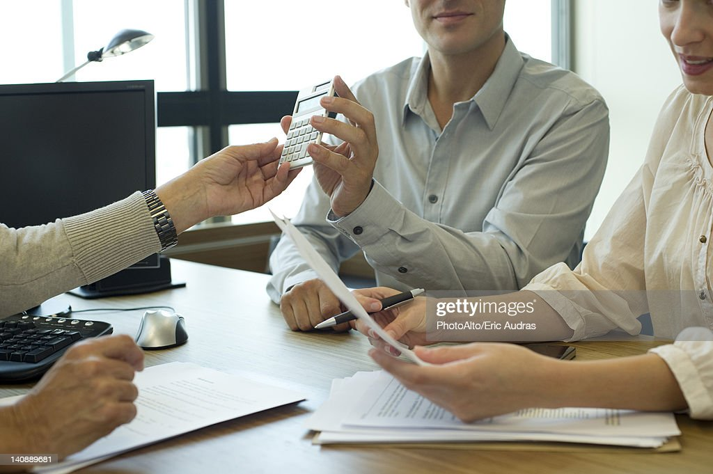 Business associates negotiating deal, cropped : Stock Photo