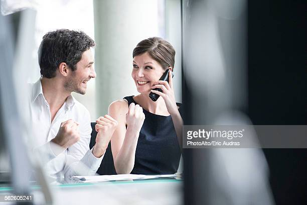 Business associates pleased by good news phone call