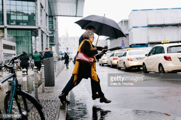 business associates running for cab in rain - stepping stock pictures, royalty-free photos & images