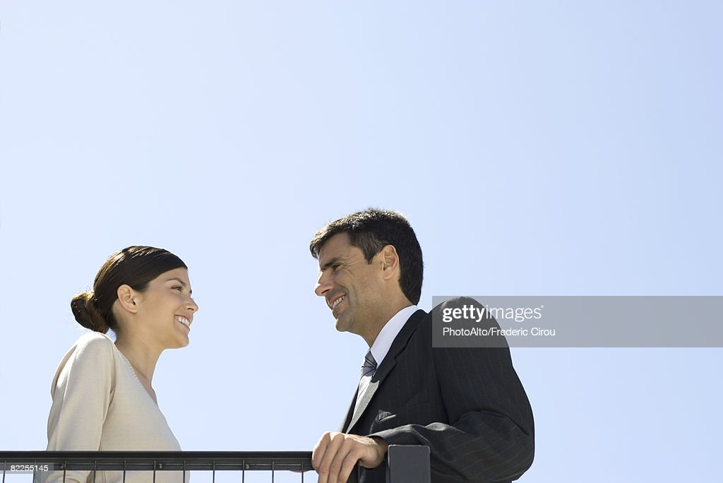 Business associates standing outdoors, smiling at each other, low angle view : Stock Photo