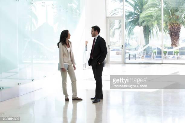 business associates talking in office corridor - 中距離 ストックフォトと画像