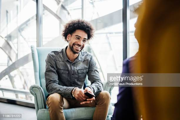 business associates talking with each other in office - homme maghrebin photos et images de collection