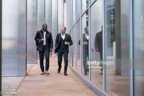 コーヒーブレイクで歩いたり話したりするビジネスアソシエイト - 接近する ストックフォトと画像