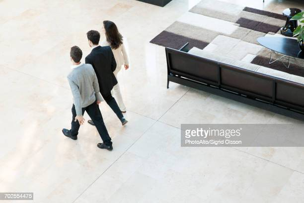 business associates walking together in office lobby - mid distance stock pictures, royalty-free photos & images