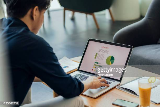 business at a coworking space: a financial analyst working at a community space - economist stock pictures, royalty-free photos & images