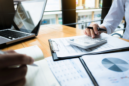 business audits using a calculator financial data investment fund at a workplace, wealth concept 1129810557